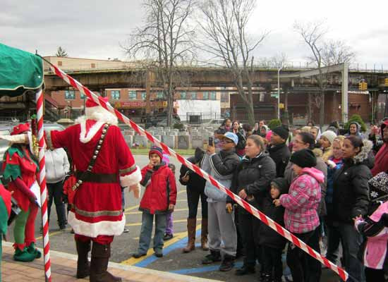 Santa in front of a crowd with is elves